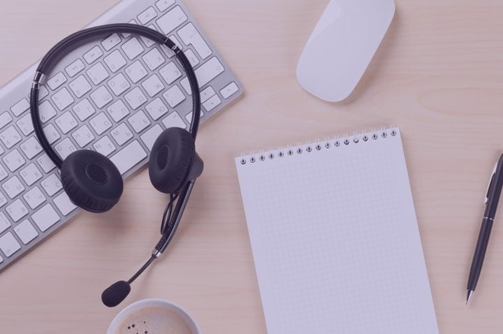 Headphones, keyboard and notepad on a desk